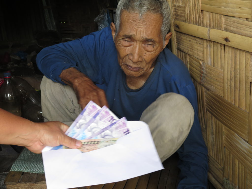 Photo is an image of an elderly man being given cash from his limited social pension.