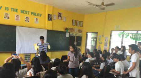 Image of a teacher inside a full elementary school classroom.