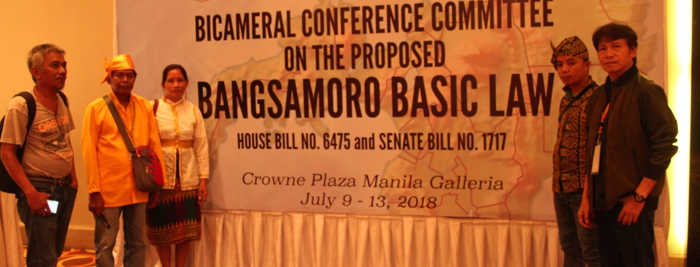 Indigenous Peoples Leaders standing in front of a banner of the Bicameral Conference Committee in the Proposed Bangsamoro Basic Law